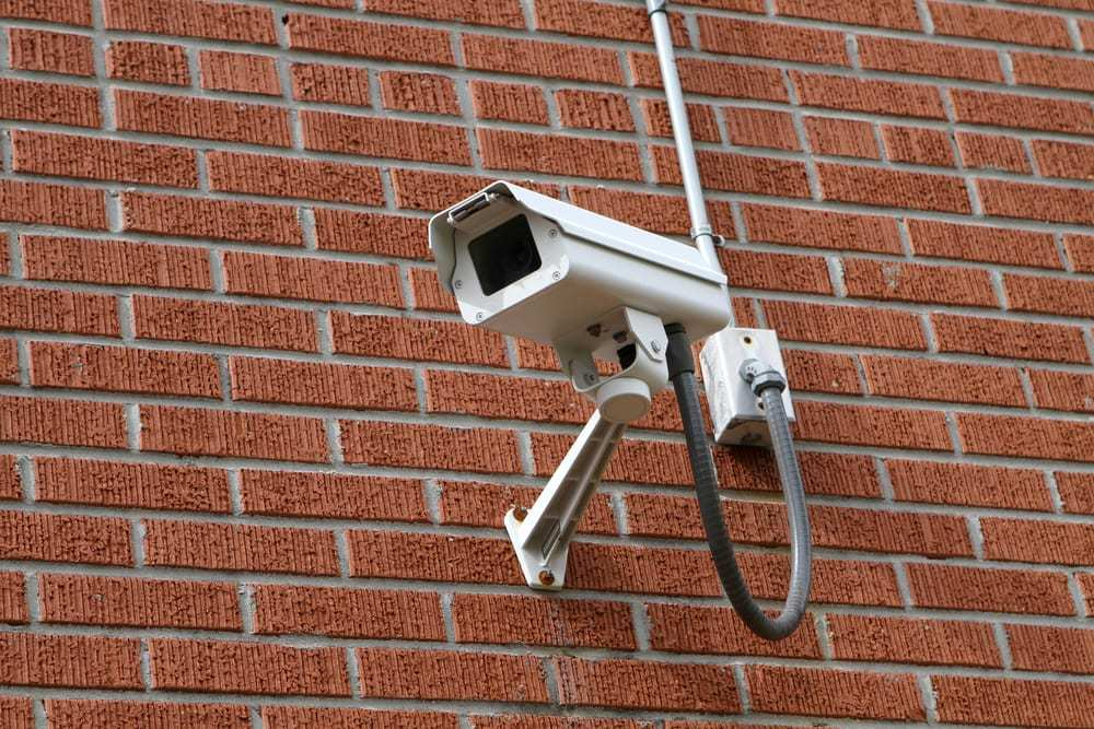 Surveillance video camera mounted to a brick wall outside a building for security