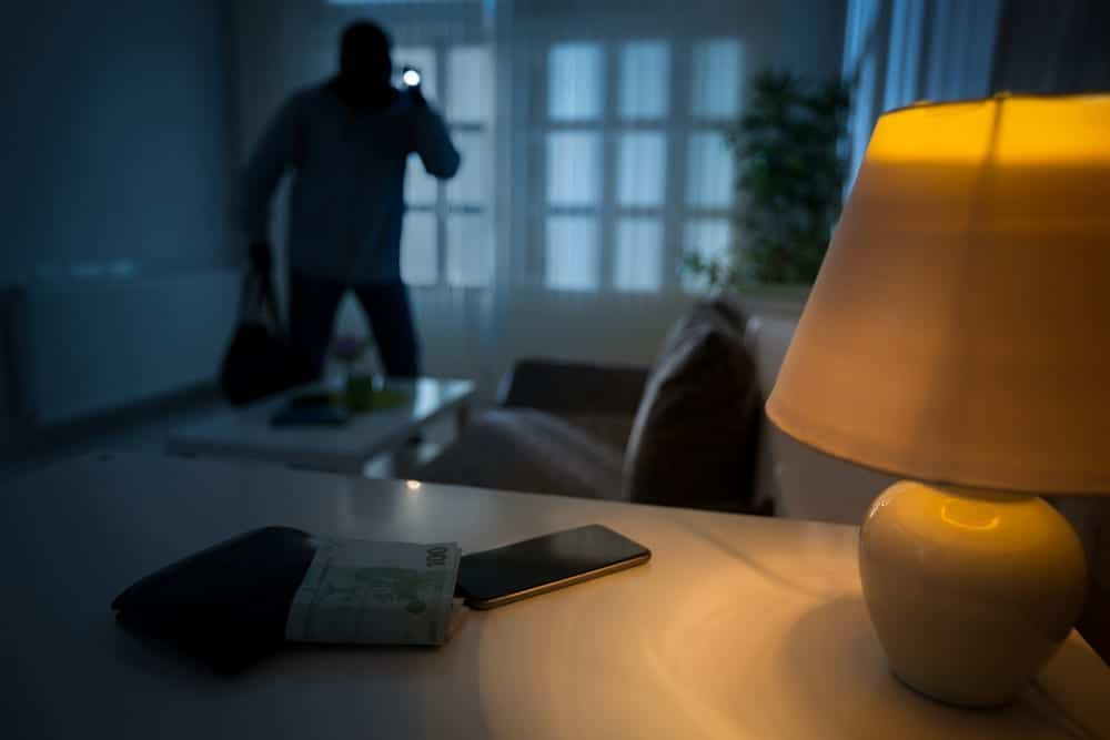 burglar with flashlight in unlit house